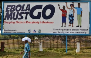 A man walks past an ebola campaign banner with the new slogan 'Ebola Must GO' in Monrovia on February 23, 2015 (AFP Photo/Zoom Dosso)
