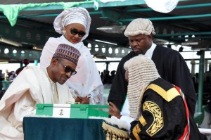 Nigerian President Mohammadu Buhari (L) sits beside his wife Aisha, as he signs a document after taking an oath during his inauguration in Abuja, on May 29, 2015 (AFP Photo/)