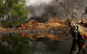 A man walks away as crude oil spills from a pipeline in Dadabili, Niger state, April 2, 2011. (Afolabi Sotunde / Courtesy Reuters)