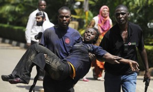 A Kenyan woman is helped to safety after shootings in a Nairobi shopping mall