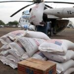 People in Jonglei state, South Sudan, unload aid from the U.N. World Food Program in January 2012