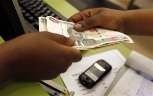 A customer conducts a mobile money transfer inside the Safaricom mobile phone care centre in the central business district of Kenya's capital Nairobi