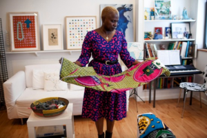Musician and author Angelique Kidjo looks at fabric before heading to her stylist's studio forafitting. Natalie Keyssar for The Wall Street Journal