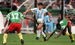 Argentina's Diego Maradona juggles with the ball as he runs past Cameroon's Benjamin Massing. Photograph: Daniel Garcia/AFP/Getty Images