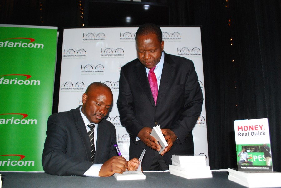 Dr. Tonny Omwansa signing the book for ICT Cabinet Secretary Dr. Fred Matiang'i