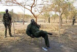 South Sudan's rebel leader Riek Machar sits in the bush as he talks on a phone in a rebel-controlled territory in Jonglei State