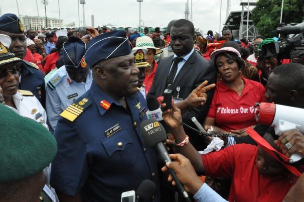 Gbenga Olamikan/AP - Air Chief Marshal Alex Badeh, the government's chief of defense staff, center, speaks during a demonstration Monday calling on the government to rescue the kidnapped girls.