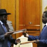 South Sudan's rebel leader Riek Machar (R) and South Sudan's President Salva Kiir (L) exchange signed peace agreement documents in Addis Ababa May 9, 2014. REUTERS/Goran Tomasevic