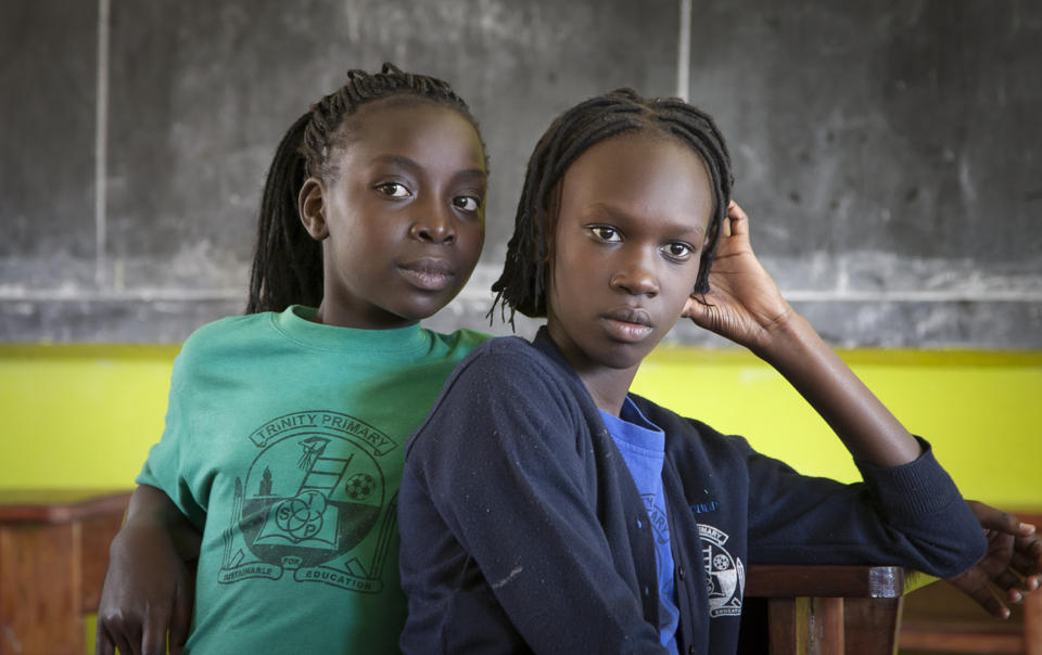 "In this photo taken Wednesday, April 9, 2014, two South Sudanese teenagers who previously lived in Israel listen to their friends reminisce about their time in Tel Aviv, in a classroom at the Trinity boarding school where they now live in Kampala, Uganda. Some 70 South Sudanese teenagers are attending boarding school in Kampala, their new home after they were deported from Israel, or voluntarily left, and after spending months in South Sudan, a country in which they struggled because of the threat of hunger and tropical diseases, the teens later were relocated to Uganda thanks mainly to the work of an Israeli activist who has criticized his country's policy toward African migrants as Israel's ""moment of shame."" (AP Photo/Rebecca Vassie)"