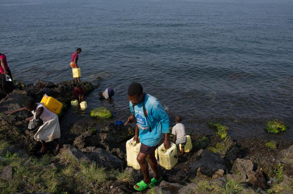 People fill jerrycans with water from Lake Kivu on the Himbi beach in Goma, in the east of the Democratic Republic of Congo on August 11, 2013 (AFP Photo/Phil Moore)