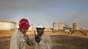 Workers for China Petroleum Engineering & Construction Corp. (CPECC) talk on a mobile handset by oil storage tanks near Melut, in the Upper Nile, Sudan.Photographer: Trevor Snapp/Bloomberg