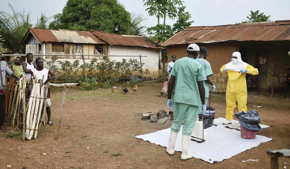 Locals watch workers with Doctors Without Borders at a private clinic working to combat the spread of the Ebola virus in Teldou, Guinea, July 10, 2014. Samuel Aranda/The New York Times/Redux