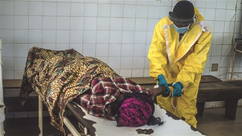 Photo: Tommy Trenchard/IRIN A health worker extracting blood to test a patient for Ebola