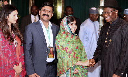 Pakistani education activist Malala Yousafzai (L) watches on July 14, 2014 Nigerian President Goodluck Jonathan look at a book at the State House in Abuja. Malala on July 14 urged Jonathan to meet with parents of the schoolgirls kidnapped three months ago by Boko Haram. Malala, who survived a Taliban assassination attempt in 2012 and has become a champion for access to schooling, was in Abuja on her 17th birthday to mark the somber anniversary of Boko Haram's April 14 abduction of 276 girls from a secondary school in the northeast Nigerian city of Chibok. AFP PHOTO -