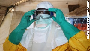 A picture taken on June 28, 2014 shows a member of Doctors Without Borders (MSF) putting on protective gear at the isolation ward of the Donka Hospital in Conakry, where people infected with the Ebola virus are being treated. The World Health Organization has warned that Ebola could spread beyond hard-hit Guinea, Liberia and Sierra Leone to neighbouring nations, but insisted that travel bans were not the answer. To date, there have been 635 cases of haemorrhagic fever in Guinea, Liberia and Sierra Leone, most confirmed as Ebola. A total of 399 people have died, 280 of them in Guinea. AFP PHOTO / CELLOU BINANICELLOU BINANI/AFP/Getty Images