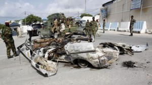 Somali soldiers stand near the wreckage of car bomb that was detonated at the main gate of the presidential palace in Mogadishu, July, 9, 2014.