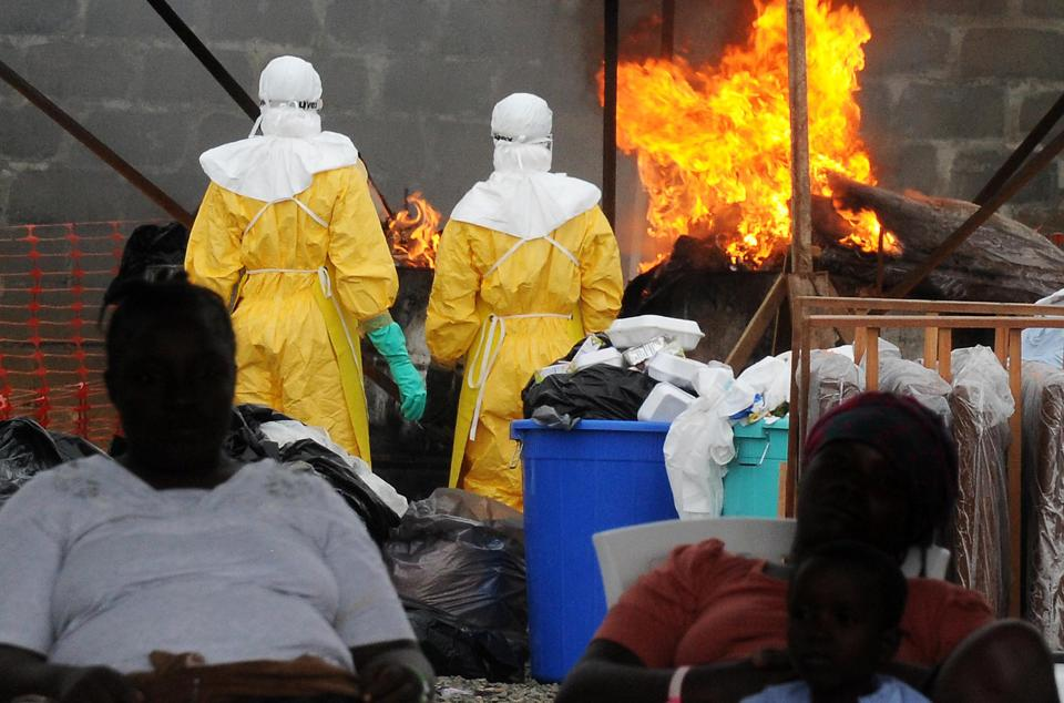 Health care workers wearing full body suits burn infected items at the Elwa hospital run by Medecins Sans Frontieres in Monrovia on August 30, 2014 (AFP Photo/Dominique Faget)