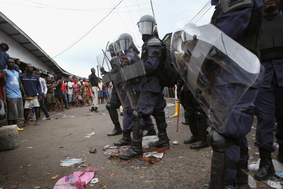 Riot police hold people back at the West Point slum in Monrovia, Liberia. The slum was quarantined following the Ebola outbreak, leading to protests from residents. Photo: John Moore/Getty Images