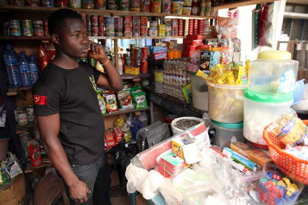 Kingsley Adukpo stands in his shop in Accra on February 11, 2014. Adukpo had to repeatedly raise his prices due to the weakening Cedi (Ghanaian currency). Ghana's trade balance has worsened. The current account deficit has risen from an average of eight per cent of GDP before it started exporting oil to 13 per cent last year. AFP PHOTO   CHRIS STEIN