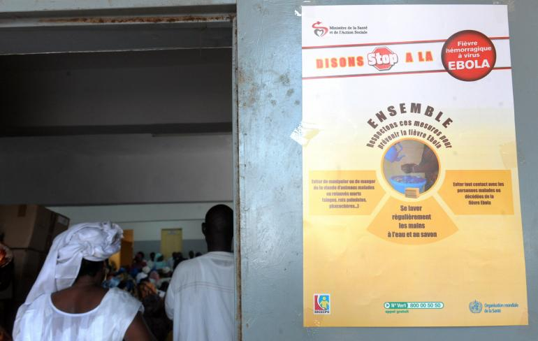 People stand in town hall of Les Parcelles Assainies district in Dakar where is posted an Ebola prevention poster on September 11, 2014. The country has managed to stave off the Ebola outbreak that has hit many of its west African neighbors