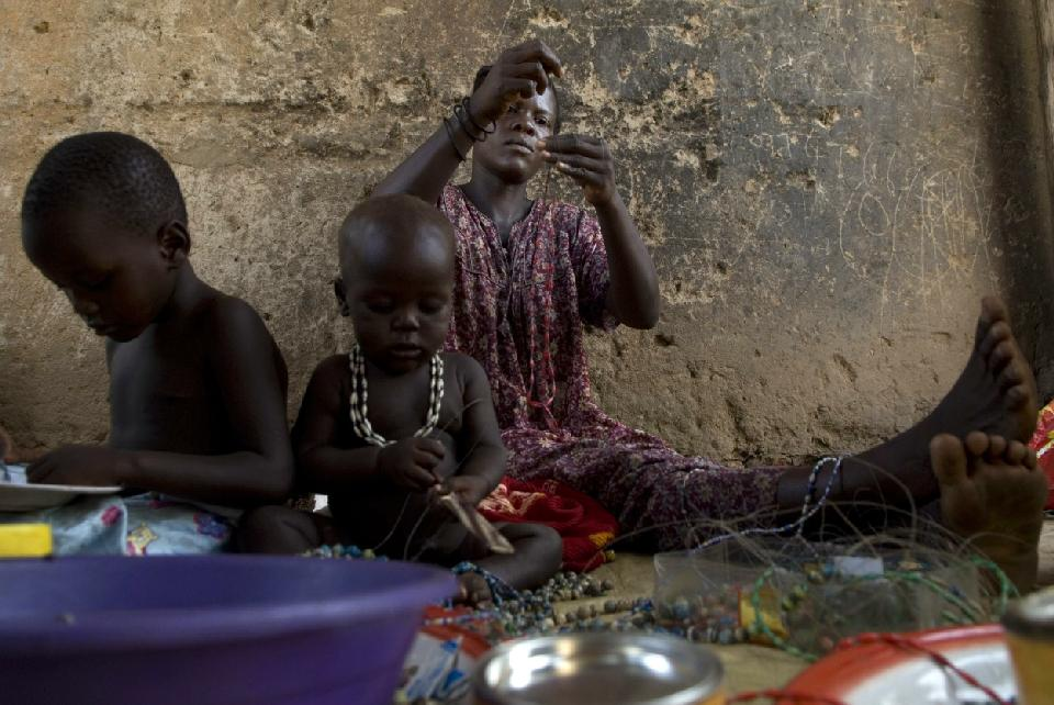 A Ugandan woman makes paper beads with the help of her children on March 1, 2008, at their home in the Namuwungo slum in Kampala (AFP Photo/Walter Astrada)