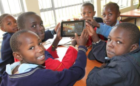 Photo: Julius Mwelu/Urban Gateway School children hold up one of the Samsung tablets used at the library.
