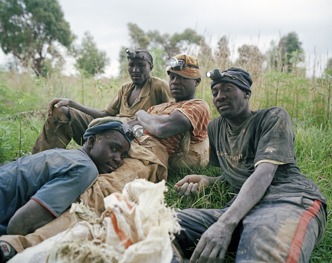 Linda Ndlovu, Daniel Mandlo, Dumisani Mahlangu, and Calvin Sibanda rest after a full night of work in a disused underground gold mine shaft. The men are highly skilled informal diggers with many years of experience. They are commonly confronted by criminals, who beat them and rob them of clothes, mining equipment, and money.