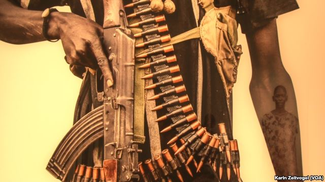 """The image of a Dinka woman is reflected in the arm of a Nuer fighter in this photograph from U.S. photographer Tim Freccia's series on South Sudan, """"Life and Death."""""""