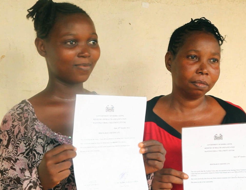 In this grab from video provided by Associated Press Television on Wednesday, Oct. 22, 2014, Ebola survivors Hawanatu Turay, left and an unidentified woman, display their certificates, after being given the all clear, at a treatment centre at Hastings, near Freetown, Sierra Leone. Dozens of Ebola survivors were discharged from a treatment center near Sierra Leone's capital on Wednesday and told they were virus-free. The third group released from the Hastings Treatment center, which included 45 patients, were also issued with health certificates they proudly held up. (AP Photo/Associated Press Television)