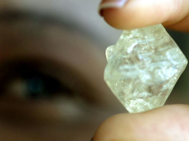 A worker at the Botswana Diamond Valuing Company displays a rough diamond during the sorting process at the purpose-built centre in the capital Gaborone, August 26, 2004. (Juda Ngwenya/Courtesy Reuters)