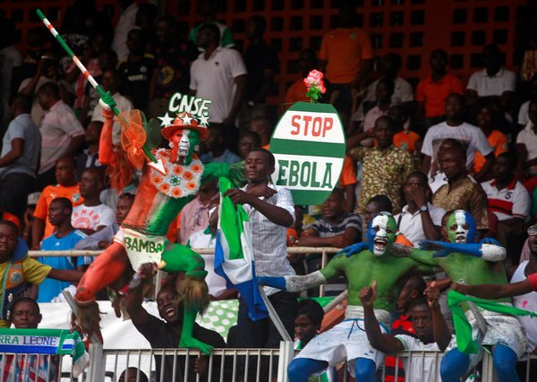 """Fans with a sign saying """"Stop Ebola"""" during a September qualifying match between Ivory Coast and Sierra Leone for the 2015 Africa Cup of Nations. Credit Luc Gnago/Reuters"""