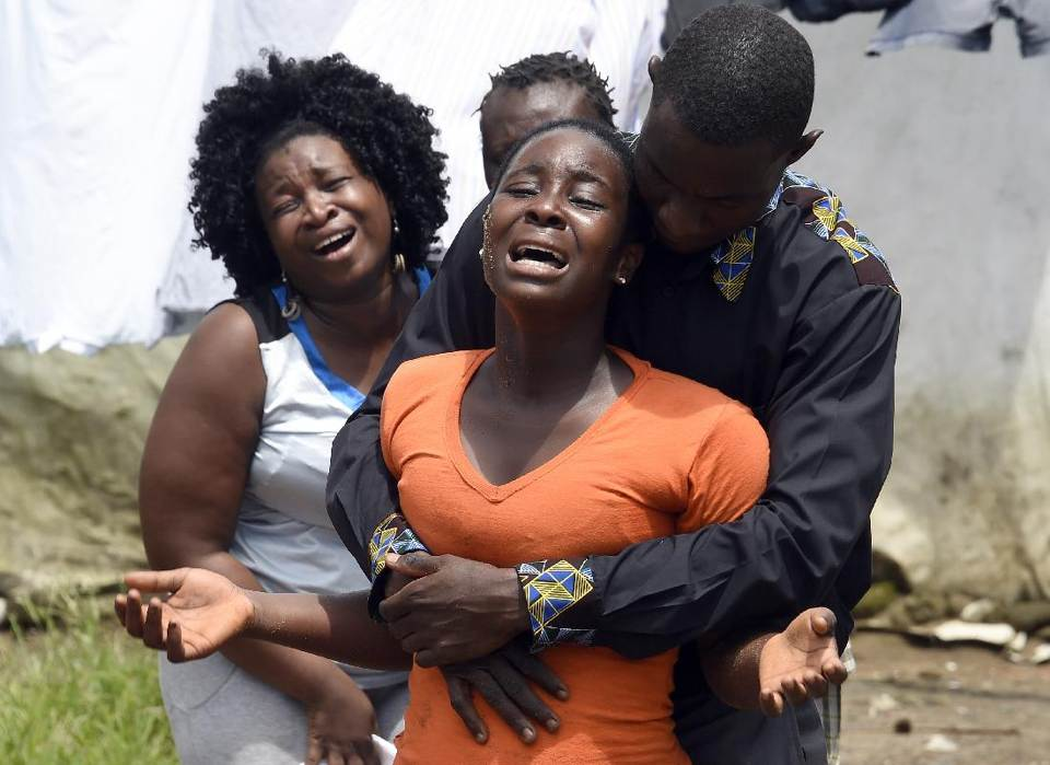 A woman (C) reacts after her husband is suspected of dying from the Ebola virus, in the Liberian capital Monrovia, on October 4, 2014 (AFP Photo/Pascal Guyot)