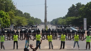 Police hold hands as they cordon off access to the parliament on October 29, 2014 in Ouagadougou, during a demonstration (AFP Photo/Issouf Sanogo)