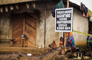A child, center, stands next to a signboard reading 'Police order quarantined home unauthorised should keep off' as a family home is placed under quarantine due to the Ebola virus in Port Loko, Sierra Leone, Wednesday, Oct. 22, 2014. U.S. authorities said Wednesday that everyone traveling into the U.S. from Ebola-stricken nations will be monitored for symptoms for 21 days. That includes returning American aid workers, federal health employees and journalists, as well as West African travelers. The program will start Monday in six states that represent 70 percent of people arriving from Liberia, Sierra Leone and New Guinea, said the Centers for Disease Control and Prevention. (AP Photo/ Michael Duff)