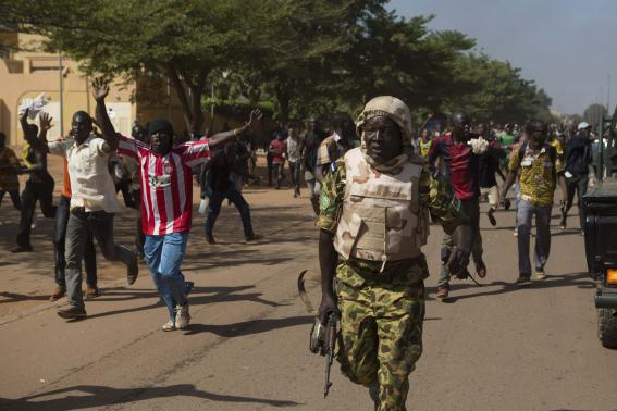 A soldier runs from anti-government protesters as they take over the parliament building in Ouagadougou, capital of Burkina Faso, October 30, 2014. CREDIT: REUTERS/JOE PENNEY