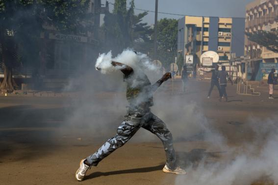 An anti-government protester throws a tear gas canister at riot police in Ouagadougou, capital of Burkina Faso, October 30, 2014.  CREDIT: REUTERS/JOE PENNEY