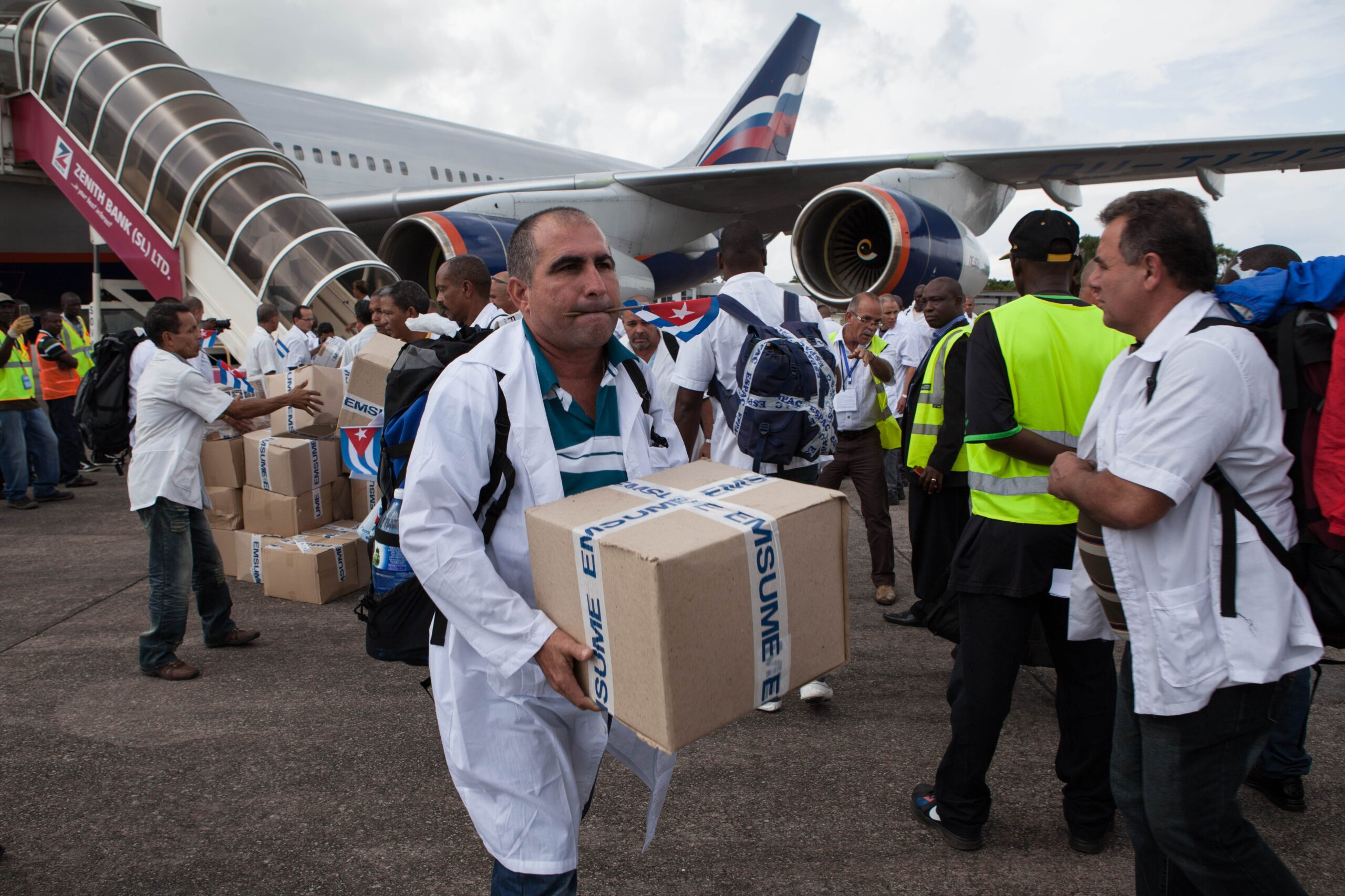 The first members of a team of 165 Cuban doctors and health workers unload boxes of medicines and medical material from a plane upon their arrival at Freetown's airport to help the fight against Ebola in Sierra Leone on Thursday.   AFP-JIJI