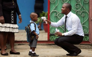 A school official takes a pupil's temperature in front of the school premises in Lagos (Reuters)