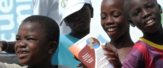 Boys smile as one reads an Ebola prevention flyer in a suburb of Dakar on September 11, 2014. (SEYLLOU/AFP/Getty Images) | SEYLLOU via Getty Images