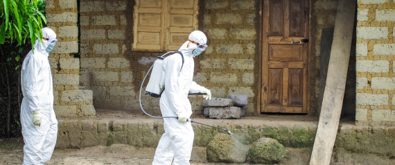A healthcare worker in protective gear sprays disinfectant around the house of a person suspected to have Ebola virus in Port Loko Community, situated on the outskirts of Freetown, Sierra Leone, Tuesday, Oct. 21, 2014. | ASSOCIATED PRESS