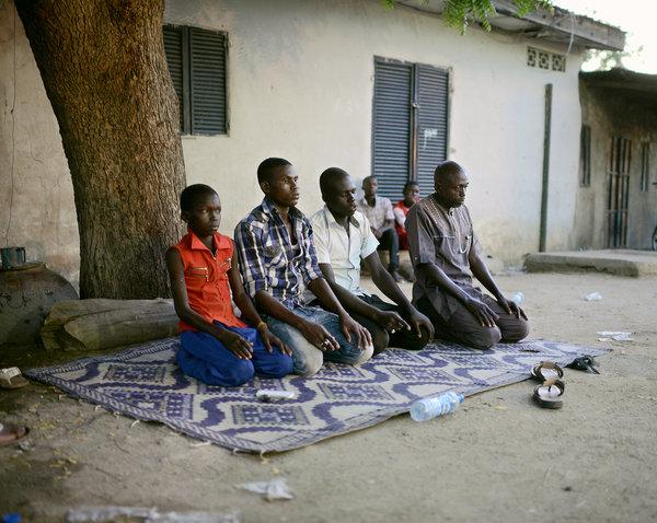 Prayer break. Kalli, far right, outside his office. Credit Benedicte Kurzen/Noor images