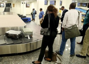 Passengers pick their bags at the arrivals section of the airport.