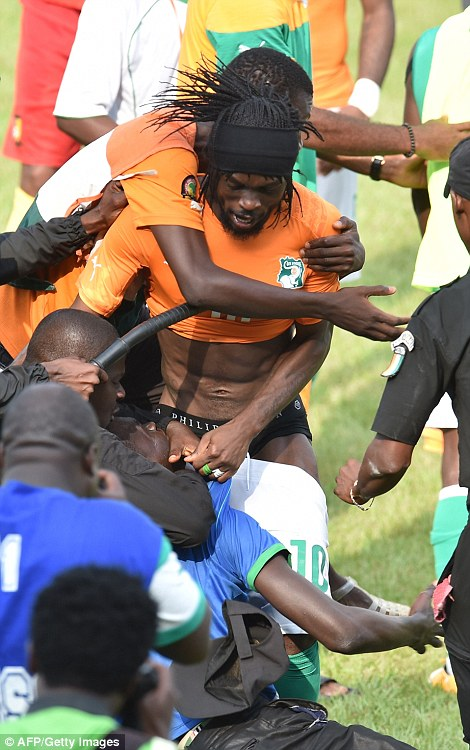 Gervinho is mobbed at full-time (left), while the supporter who grabbed him at full-time is dragged away by police (right)