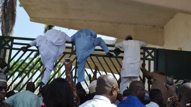 Unidentified lawmakers scale the parliament gate, in Abuja, Nigeria. Nov. 20, 2014.