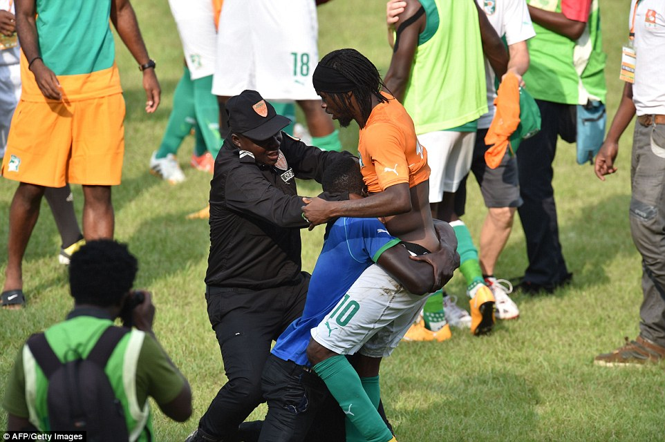 A policeman tries to pull a supporter away from Gervinho at full-time, after he grabbed the Ivorian forward