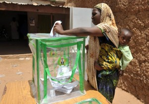 A file picture taken on April 16, 2011 shows a Nigerian woman carrying her baby and casting her ballot as she votes at a polling station during Nigeria's presidential elections in Daura (AFP Photo/)