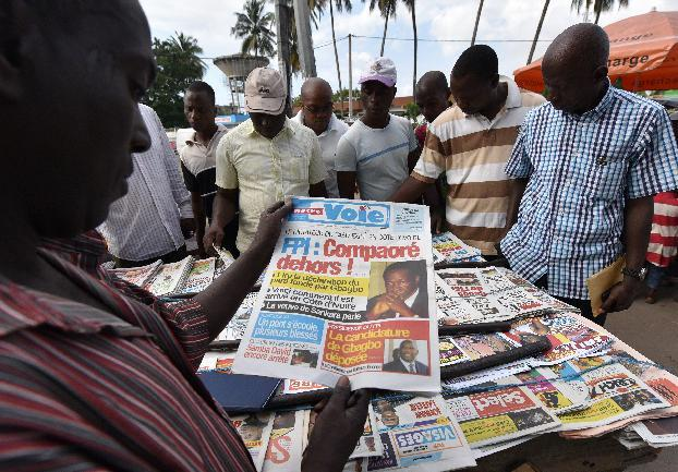 "A man looks at a newspaper bearing headlines on the situation in Burkina Faso and reading ''Compaore out!"" on November 3, 2014 in Abidjan (AFP Photo/Sia Kambou)"