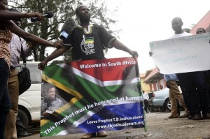 A member of the Synagogue Church of All Nations holds a placard of a South African flag with the picture of Nigerian preacher and SCOAN leader TB Joshua on November 5, 2014 (AFP Photo/Pius Utomi Ekpei)