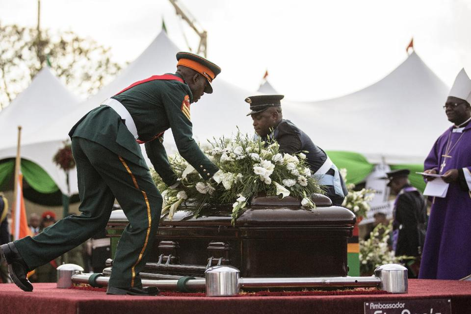 Zambian Armed Forces lay flowers on the casket of the late Zambian president ahead of lowering it into the grave during his state funeral on November 11, 2014 at Embassy Park in Lusaka (AFP Photo/Gianluigi Guercia)