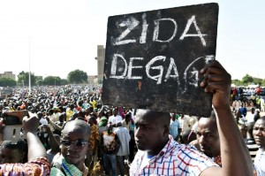 "A man holds up a placard that reads in French, ""Zida get out"", referring to Isaac Zida, a high-ranking officer named by the military to lead the country's transition, during a protest in Ouagadougou on November 2, 2014 (AFP Photo/Issouf Sanogo)"